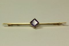 Gold and amethyst stock pin