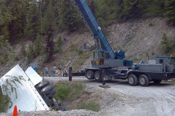 large blue crane attempts to lift a large white over turned semi from side of mountain cliff