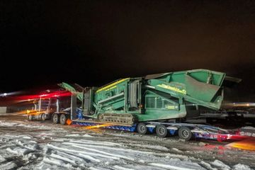 tow truck tows large piece of heavy machinery down a snowy road at night