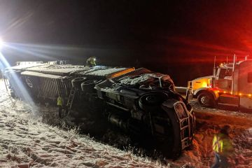large semi truck over turned on the side of the highway at night in the snow