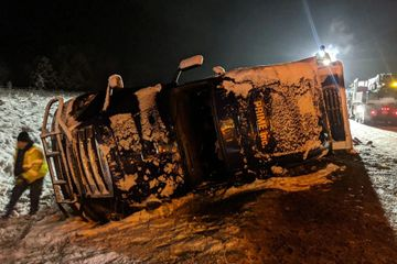 over turned semi covered in snow on the side of the road at night