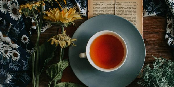 filled TEA CUP WITH BOOK ON TABLE WITH yellow FLOWERS