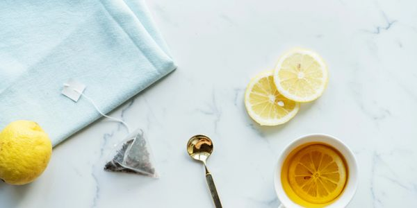 white TEA mug WITH LEMON AND golden SPOON ON MARBLE WHITE COUNTER, tea sachet and blue napkin