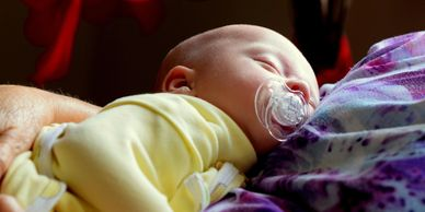 Infant baby sleeping on lap.