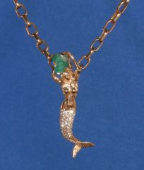 Mermaid in 14K Gold, holding raw 1K Emerald and Diamond covered tail