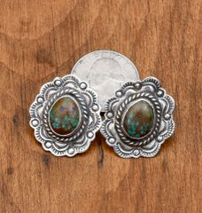 Ornately stamped dead-pawn Navajo Sterling earrings with turquoise center.