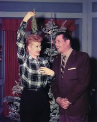 Desi Arnaz smiles as Lucille Ball holds a mistletoe over her head while filming the famous, Christmas Show 8x10