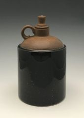 Black little jug with decorative stopper top.
