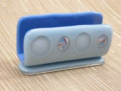 Blue glass business card stand with decorative swirls