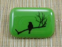 Bird on a branch brooch - green glass