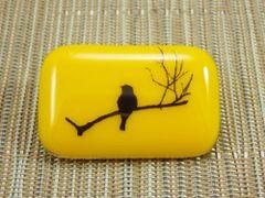 Bird on a branch brooch - yellow glass