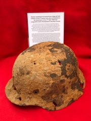 Battle damaged German soldiers M40 helmet recovered from a large pit used by soldiers of the 5th Panzer Army who surrendered to the Americans on the 17th April 1945 near Langenfeld south of Dusseldorf in the Ruhr Pocket