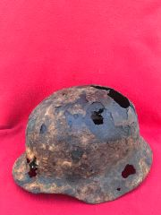 German soldiers M35 steel helmet with some green paint remains and complete liner ring,battledamage recovered from a large pit of German equipment recovered near village of Trun in the Falaise Pocket on the Normandy battlefield of 1944