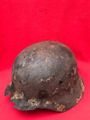 German soldiers M40 steel helmet with some green paint remains and liner ring recovered from a large pit of German equipment recovered near village of Trun in the Falaise Pocket on the Normandy battlefield of 1944