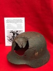 German Soldiers M40 helmet with decal,paintwork, battle damage recovered from near Bialystok which was a Russian pocket of resistance during Operation Barbarossa the invasion of Russia in June 1941