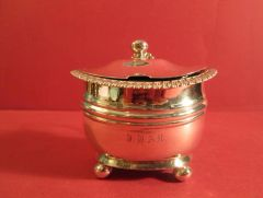 Sterling silver mustard pot, oval shape with gadrooned lid, on four ball feet. Monogrammed on the side, Newcastle, 1818.
