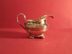 Sterling creamer with gadrooned border on four ball feet. London, 1787, by Jon. Keith