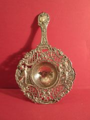 Dutch tea strainer, silver, with repoussé border and handle; early 20th century.