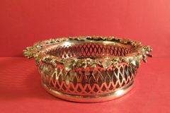 English silver coaster with cast border, pierced sides and wood base with sterling center button. London, ca. 1860.
